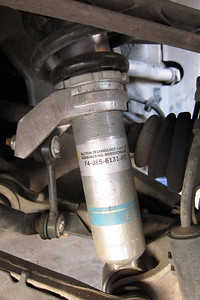 This photo is courtesy of a local 1995 Porsche Carrera C4 (993) owner. This photo is with the car on a lift.  The strut is the popular Bilstein B6 (known as Bilstein HDs on many forums) and the spring is a Porsche spring (brown paint mark).  Note that the adjustment collar that the spring makes contact with is in the fully up position. Normally, you would want some threads above and below the adjustment collar to allow for ride height adjustment. Ride height according to the owner as adjusted is 117 mm.