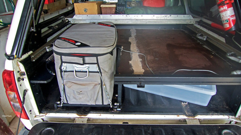 """DIY deck in my Nissan Navara D40 dual cab. As I had all the materials to make it, was no use me paying some $1200 plus (incl freight) to buy a factory setup. A 4x4 mate was going to dump the two big sheets of structural 'Form Ply' so he was good enough to drive the 32k out to our place to see if I wanted it. """" Yes please """" All the steel and aluminium was re-cycled at least once. Sure, I had to buy a factory fridge slide (could make one if I really wanted to) but if I had the factory deck, still would have to add the fridge slide to the bill. Slide is high quality steel and sealed ball bearings and glides just so smoothly, even when fridge is loaded. Note the ripper shelf I made way back behind the cabin. Holds heaps. Easy port window access."""