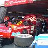 Kasey Kahne, is under his car hiding from Suzanne.<br /> A good shot of his rear (not the car) and the bottom of his shoes.