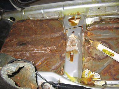 "Passenger side after carpet removal.  4"" area rusted through near sill."