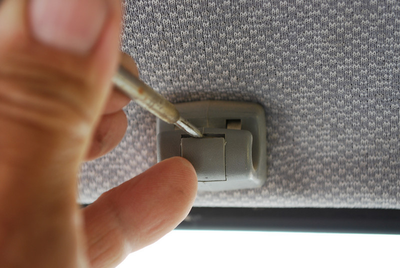 To access the screw for the right sunvisor mount use a small screwdriver and pry the plastic cover open from the top.