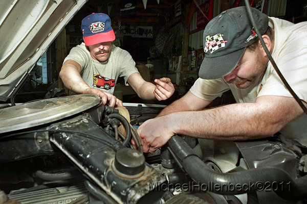 Robert Olson and Curt McGill reinstall the distributor into their 1980 Ford Mustang assembled for Autocrossing events.