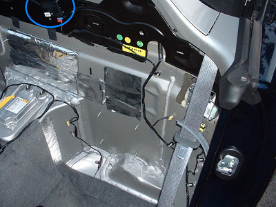 Highlighted here is the actuator for the trunk release.  The four studs on the bulkhead behind the driver's seat are where the amplifier mounts in a Monsoon-equipped Solstice.  The electronic box on the driveshaft tunnel is the airbag system computer, if I recall correctly.