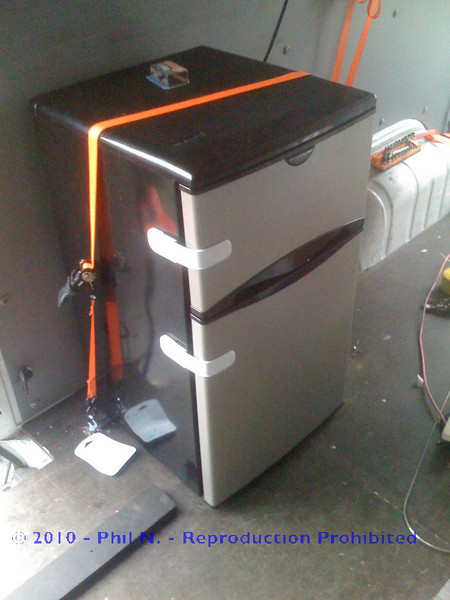"""Our fridge - running off of our 1500W Xantrex inverter - We spent two nights in campgrounds and never hooked up to shore power to run the fridge - the driving charged the aux. battery enough to run the fridge with the truck off for about 8 hours - I don't know how long it will actually power the fridge without running - but it certainly served our purpose well!  (Battery monitoring of some sort will be added soon!!)<br /> <br /> The fridge has a """"channel"""" at the back of it, there's a piece of 1"""" bar stock running through that, then two eye-bolts through the floor with fender washers and lock nuts on the bottom to secure the ratchet straps to - it's solid and not movin'!! - and pretty easy to remove...Next step here is to weld nuts to the bottom of the van so it can be completely removed/replaced from inside without going under the van or laying on the ground..<br /> <br /> Part of our trip included some hotels/lodging, so, we did have to take it out and put it in our room to keep it running while the van was parked and not moving for a couple of days in a row.."""
