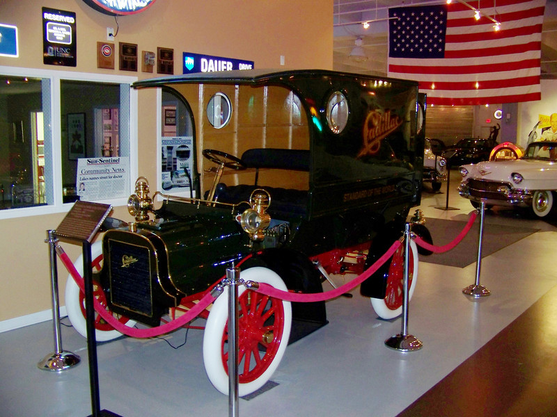 """1906 CADILLAC MODEL M DELIVERY WAGON<br /> Production: 2659 (all models)<br /> Factory Price: $950<br /> Engine: 98.2 cubic inch, one cylinder 10 horsepower<br /> <br /> Three years after the first Cadillac was offered to the public as a single model, this delivery wagon was introduced. The horizontal single cylinder """"Little Hercules"""" engine is mounted under the front seat and uses an updraft mixer (carburetor) to develop it's ten horsepower at 900 RPM. The engine must be hand cranked to start. The two speed planetary transmission's low speed band is operated by the left foot pedal, while the high speed and reverse bands are engaged by the large lever on the right hand side of the vehicle. The steering is a rack-and-pinion design."""