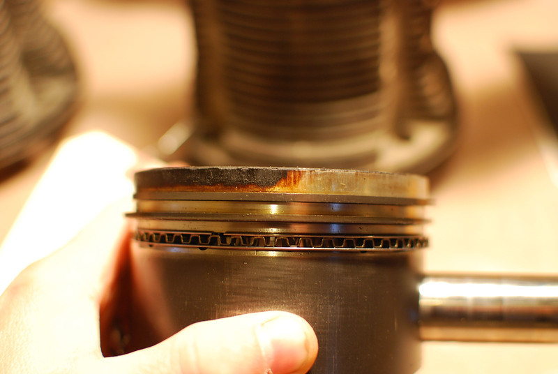 You can see the piston was not sitting in the cylinder squarely.  One side of the piston above the compression ring was rubbing hard and is carbon-free, the other side has substantial space and has high amounts of carbon buildup.