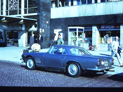 Maserati 3500 GTi Europe. Bob behind and someone checking out the car. We were probably parked at that bank to make a cash withdrawal because the car was bankrupting us.
