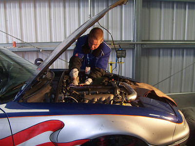 HANDS ON -- Team A+Racing mechanic Spencer Doty of Loomis makes topside adjustments as the new clutch goes in on the sleek blue, red and silver 60, which ultimately finished ninth. .