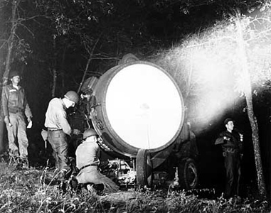 The only reserve searchlight unit in the United States Army, Battery E, 29th Artillery, sights in an 8-million candle-power light during their proficiency tests at Camp McCoy, Wis., where they participate in annual summer training.  The citizen-soldiers are members of the 2nd Platoon, from Milan, Ind.