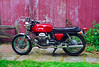 I bought this 1973 Moto Guzzi V-7 Sport new but maintained and stored it poorly. In this 1992 picture it is just back from its first frame-off restoration. Obviously non-standard are the aftermarket silencers, as stock units were no longer available. It is also missing decals. Less obvious is that the tank and side case color is not original. The paint shop matched the faded color they got it with. It has since been repainted and decals applied<br /> <br /> A persistent electrical problem led me to trust it to the last remaining ex-Berliner dealer in southern New England. <br /> <br /> He turned out to be an incompetent charlatan.