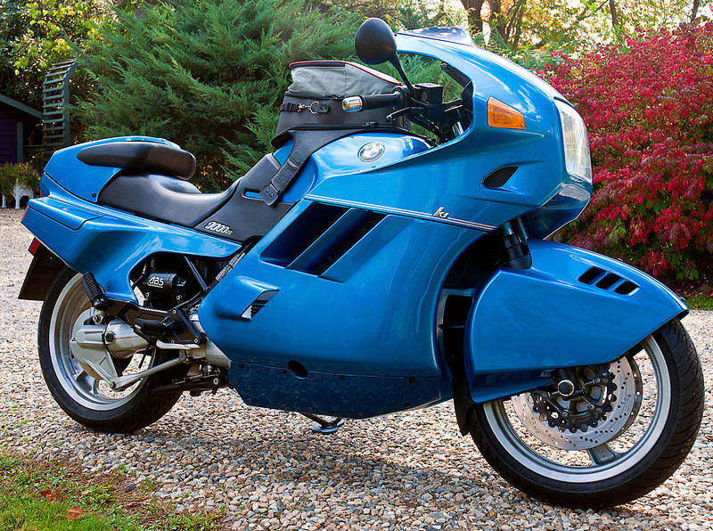 BMW developed the liquid-cooled, in-line four cylinder 1000cc K 100 to change the two-wheel world's idea that they only could make flat-twin tourers.<br /> <br /> The K-1 took that platform into the sport class.<br /> <br /> To cope with the 100 bhp limit, the designers used aerodynamic wheel and body fairings to create one of the slipperiest production bikes with a drag coefficient of 0.34 with the rider prone.<br /> <br /> Though rumored to have issues with heat build-up, secondary vibration and panel cracking, the bike forever changed the image of the two-wheeled Beemer.<br /> <br /> Initially supplied with un-BMW color and graphics, Phil's 1993 in Silk Blue -- one of only twenty to make it to the US --  is nicely understated and must be a real sweet ride.