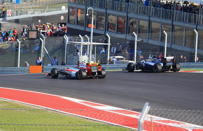 F1 cars exit turn one. Bruno Senna is on the outside.