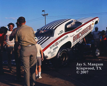 Driver of the Ramchargers funny car, Leroy Goldstein, with fans at the 1970 or 1971 NHRA Springnationals in Dallas.