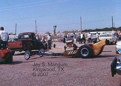 This is believed to be the A/Fuel Dragster of George Van Artsdale lining up in the pits at Green Valley Raceway, March 1965, at the AHRA Spring Grand Nationals meet. This was before aluminum custom engines, and these steel motor blocks were actual passenger car power plants removed from junkyards and beefed up to handle the stress of going 0 to 200 MPH in under 8 seconds. It took a while, but the racers eventually depleted the nation's junkyard population of genuine Chrysler hemis.