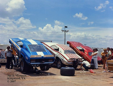 """Blue Max, Ramchargers, and Big John Mazmanian in the pits at Dallas, 1971 Springnationals.  Scenes like this at big meets with rows of funny car bodies propped into the air helped coin the phrase """"fiberglass forest"""". That weekend the pits were crammed with high quality famous dragsters from all over the U.S."""