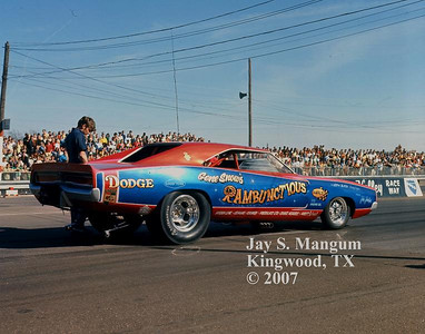 Summer 1969. Crew Chief Jake Johnston beside Gene Snow's record setting Dodge. Snow was the first funny car driver to top 200 MPH, breaking the old record by 5 MPH in this machine when he did it. Jake went on to drive the Blue Max funny car for a time with great results.