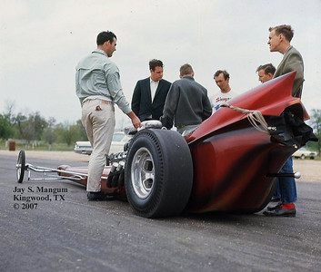 """Don Ross, Larry Brown and John Waters came to my rescue on this I.D. It is the """"Taboo"""" car owned by Wolley and McConnell of Oklahoma City, with Larry Brown (in Simpson shirt) behind the wheel. Green Valley Raceway, Texas, mid 1960's. Future fuel driver Chip Woodall is also in the photo. The day I took this picture the dragster was show car perfect. Thank you, guys!"""