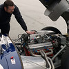 Mike works on Erickson Shirley's 1959 Costin Lister Chevrolet. The engine features a Rochester fuel injection.