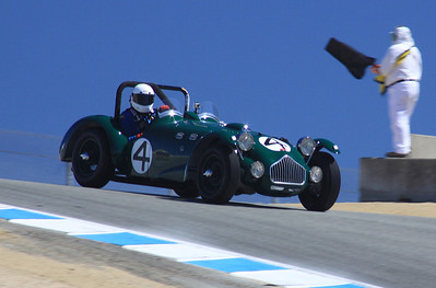 A 1950 Allard J-2 Le Mans roadster driven by Graham Smith comes over the crest at the top of the Corkscrew.