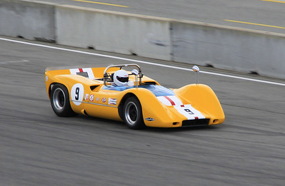 A 1968 McLaren M6B driven by Bob Lee accelerates down the front straightaway after exiting turn 11.