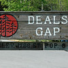 """The Tail of the Dragon straddles the rural state line between North Carolina and Tennessee; its """"starting line"""": the tiny burg of Deal's Gap, N.C., population 6. Check the sign. ;)"""