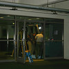 Beginning to dismantle the swinging glass doors in the lobby, leading to parking lot behind the building