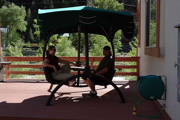 Jacob and Christine swinging in the shade next to the roaring river at the hotel.