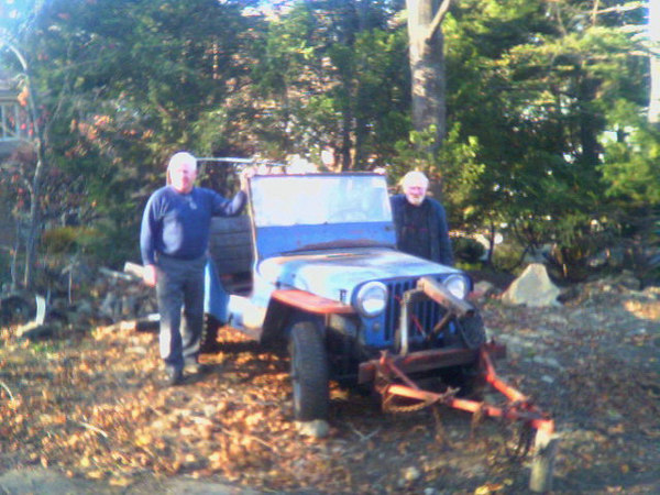 2006: The Jeep (with tow bar attached) sitting in my parent's backyard where a temporary shelter will be built over it. My dad on the left and my uncle on the right.