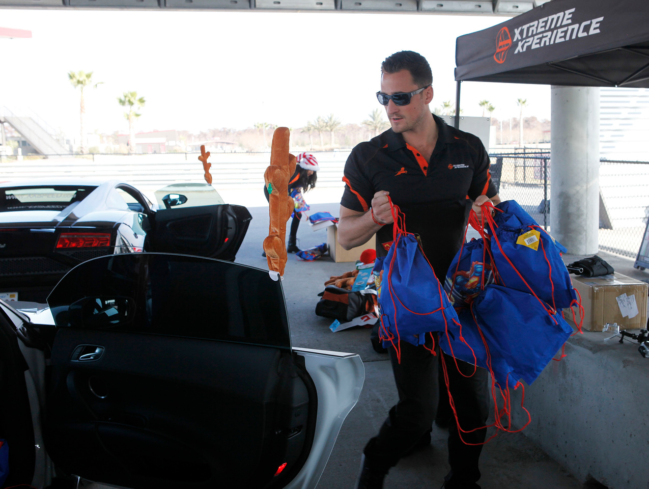 Xtreme Xperience President Adam Olalde loads bags of gifts into the XX Supercars.  (Bradley S. Pines / Xtreme Xperience)