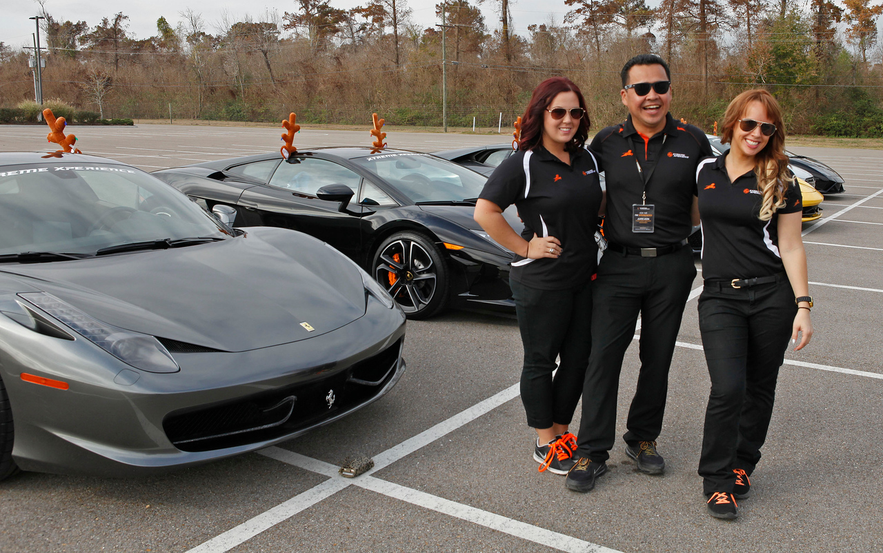 Xtreme Xperience's Alyssa Marie Butler, Juan Leon and Becky Lawrence pose with the XX Supercar fleet prior to leaving NOLA Motorsports Park. (Bradley S. Pines / Xtreme Xperience)