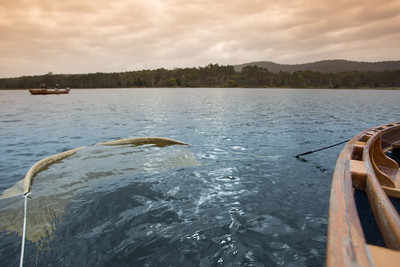 Drougue off wooden boat while fly fishing in Tasmania.