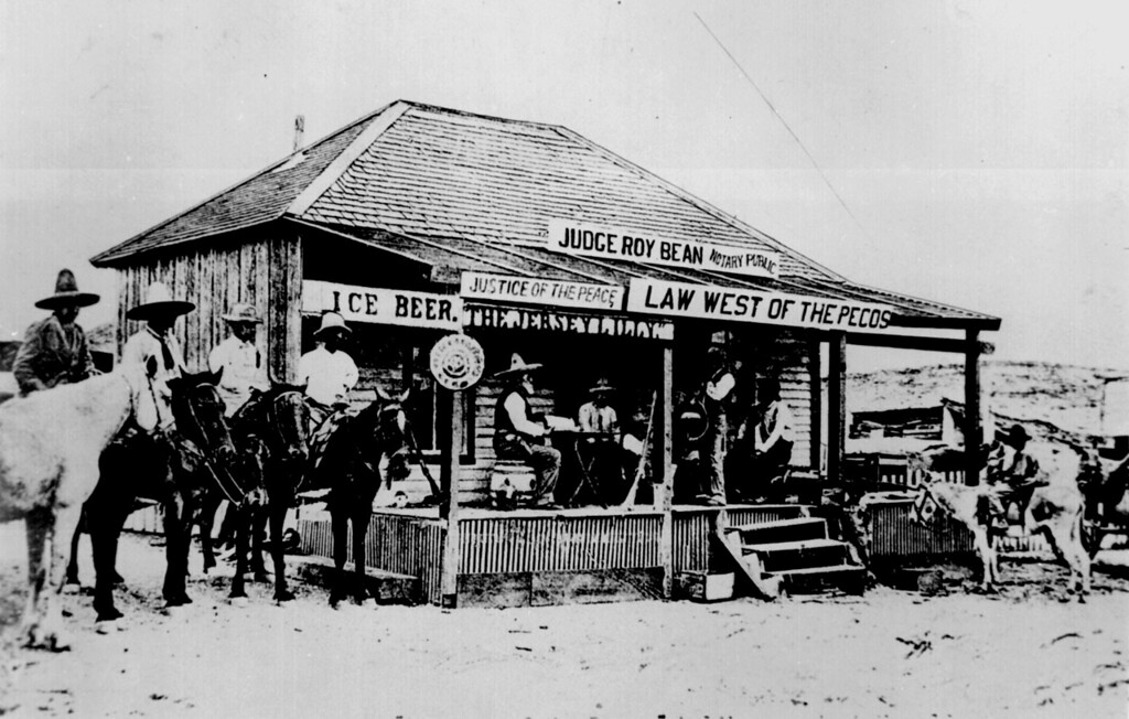 Judge Roy Bean, the `Law West of the Pecos,' holding court at the old town of Langtry, Texas in 1900, trying a horse thief. This building was courthouse and saloon. No other peace officers in the locality at that time.""