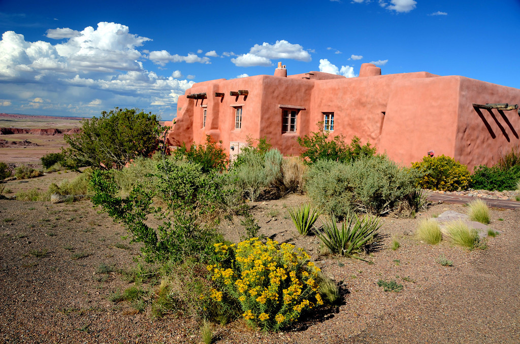"""""""The Painted Desert Inn was built in 1924 on a high perch overlooking the Painted Desert by a man named Herbert Lore in 1924. The two-story inn, nicknamed named the Stone Tree House, due to the petrified wood used in its construction, was operated as an inn and tourist attraction for almost twelve years. Meals were served in the lunchroom, Native American arts and crafts could be purchased in the curio shops, and a cool drink could be enjoyed in the downstairs taproom. Rooms were available for $2 to $4 a night. Lore also gave 2-hour motor car tours through the Black Forest in the Painted Desert below. <br /> <br /> This isolated oasis in the Painted Desert was purchased by the Petrified Forest National Monument in 1936 and began updating its electrical, plumbing, and heating systems. Guest rooms, a new entryway, a dining room and a shaded porch were added to the original structure, as well as stained glass ceiling panels, hammered tin chandeliers, and hand-carved furniture. <br /> <br /> During the Dust Bowl days, thousands of heartland residents fled west on Route 66 in search of a better life. Hollywood documented the era in The Grapes of Wrath, which included scenes at the Painted Desert Inn.<br /> <br /> During World War II, the Inn was closed, but reopened after the war was over. Shortly thereafter, the Fred Harvey Company took over the management in 1947. In no time, the legendary Harvey Girls complimented the Inn with their excellent service in the spotless dining room.<br /> <br /> A year later, the company's architect and interior designer, Mary Colter, oversaw the remodeling of the dining rooms, hiring Fred Kabotie to paint murals in two rooms that would reflect his Hopi heritage. In the same year, the Painted Desert Inn became the park's northern headquarters.<br /> <br /> Following the war, Route 66 became busier than ever as people began to experience """"vacations."""" For many, the Mother Road included a stop at the Petrified Forest, and a bite to eat or cu"""