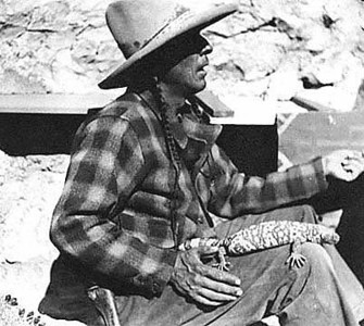 """""""Harry E. (Indian) Miller, claiming to be a full-blooded Apache Indian, and being part Mohawk, looked over possibilities at Two Guns. Well educated and possessing a flair for gaudy publicity, he leased a business site from Cundiff for a period of ten years on March 5, 1925.<br /> <br /> Miller advertised himself as """"Chief Crazy Thunder,"""" and wore his long hair braided. He had served in the Philippines with the U. S. Army following the Spanish-American War.<br /> <br /> At Two Guns he and his wife began an extensive building program. On the canyon rim he put in a long stone structure with Indian labor, in the rear of which and facing the main canyon, were wild animal cages and pens. He called this a lion farm (he had several mountain lions). The center of the building and entrance into the zoo contained a small store and living quarters.<br /> <br /> Additional small buildings were also constructed in which a restaurant and an Indian curio shop were put and operated by others. One of them was Hopi Chief Joe Secakuku.<br /> <br /> Investigating the Apache Death Cave, Miller cleaned out the first two caverns. Cliff dweller ruins were then constructed inside the entry way and first cavern. What few Apache skulls he found were sold to tourists as souvenirs. (Now and then one still comes to light). The horse and human bones were disposed of to a Winslow bone dealer.<br /> <br /> Hopi Indians hired off the reservation built a pueblo type house on the side canyon rim directly over the cave. A paved path was laid down, connecting with a wooden bridge to a land island, and lookout points to a series of openings and eroded formations adjacent to the cave."""