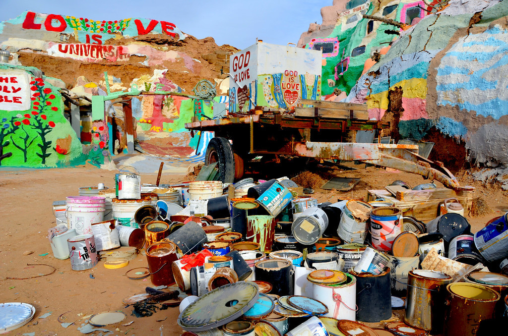 """It is estimated that over 100,000 gallons of paint have been used on the project, most of it donated.<br /> <br /> """"After ten years of relentless toil, Leonard and his mountain began to gain some notoriety. It was especially noticed by the Imperial County Supervisors. You see, Salvation Mountain as it had come to be known, was at the entrance of Slab City (the Slabs), a community of """"snowbirds"""" (visitors who live in the northern United States and Canada and travel to the warmer southern states for the winter) and local squatters occupying the old dismantled and abandoned Fort Dunlap World War II Marine training base. Only the concrete slabs of the barracks and Quonset huts remain. Because the land was government owned and because so many people were camping there without paying taxes or rent, the county thought it would start collecting a user fee. They also figured that there might be a conflict with a """"religious monument"""" at the entrance to a county campground. So in July of 1994, their solution was to hire a toxic waste specialist  to come out and take samples of the dirt around Leonard's Mountain to test for """"contaminants."""" Even before the test results were back, they cordoned off the area and labeled it a """"toxic nightmare."""" The tests predictably came back claiming high amounts of lead in the soil. The county petitioned the state of California for funds to tear down the mountain and haul it away to a toxic waste disposal dumpsite in Nevada. <br /> <br />     Local residents, and snowbirds alike, did not see that as an option for Salvation Mountain and their friend Leonard. Hundreds and hundreds of signatures were collected on circulated petitions. Thanks to the help of many old and new found friends, Leonard dug soil samples from the very same holes as the """"expert"""" had used and submitted them to an independent lab in San Diego. No one was surprised when the new tests reveled that there were no unacceptable levels of any contaminants -- especially lead -- at Salv"""