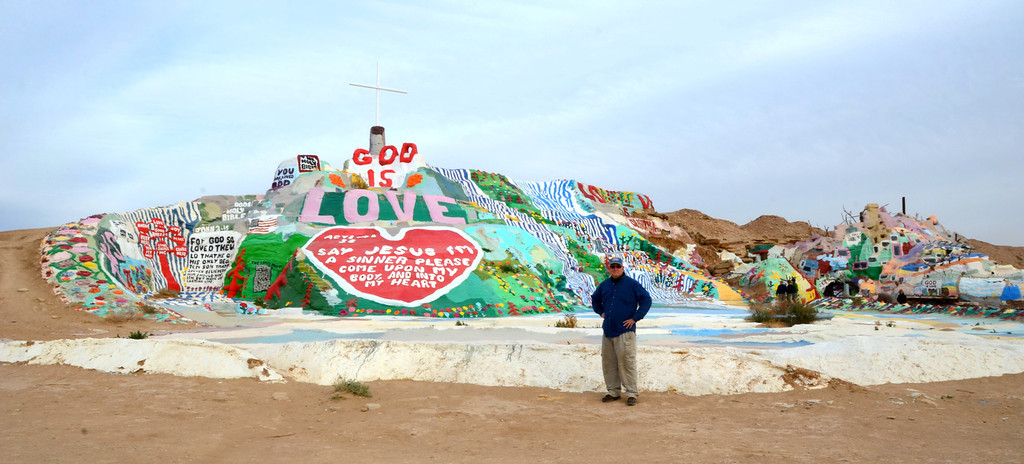 """Me at Salvation Mountain<br /> <br /> """" Leonard rises at 5:00 a.m. and heads into town for a cup of coffee. He is soon back at the mountain working the adobe clay that he has had soaking in water from the day before. There is always painting to do (if he has paint.) Leonard works on whatever he feels like at the time -- but he is always working on something. In the summer months when the temperature is usually between 105° and 120° (41°and 49°C), he is usually done with the hard stuff by 10 or 11 o'clock. During the heat of the day, Leonard likes to take a nap. As you might expect, he has very few visitors at this time of year as opposed to the winter time when upwards of 100 people and more might journey to Salvation Mountain on any given day. During these times, much of his day is taken up with showing visitors around and answering questions. The average high  temperature during the winter months is in the 60's and 70's while the average low can be in the 30's. For this reason, Leonard usually goes to bed with the sun. It's just too cold to do anything else"""""""