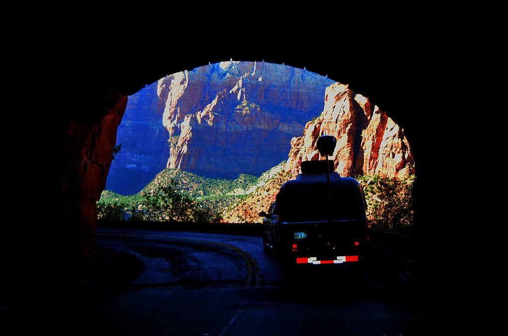 Highway 9  - Zion National Park<br /> <br /> The Zion-Mt. Carmel Tunnel is 1.1 miles long and was completed in 1930.<br /> <br /> Two ladies in a van behind me at the tunnel entrance humor me and agree to photograph me with my camera as I emerge from the tunnel. It occurred as I handed one of them my camera, that there had to be some  element of trust involved in such a transaction.<br /> <br /> The color and light are amazing as you exit the tunnel.