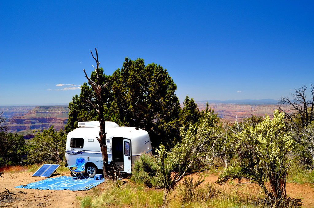 """Crazy Jug Point<br /> <br /> <br /> I  talked to a Ranger at the Kaibab Forest Information Station. I told her I was looking for a spot on the canyon rim such that if I crawled out the escape window of my Casita, I would fall 2,000 ft. She didn't miss a beat pointing out a couple of points on the map. Crazy Jug Point came pretty close to my request. I backed the trailer down a hill to position the trailer next to the shade of the Juniper. There were deep canyons on either side of the point and sweeping views of the canyon immediately behind my Casita. Cliffrose was in bloom in the foreground. Each evening I pulled  my chair over to the rim and watched the changing light.<br /> <br /> <br /> """"This point features great views and good access roads at an elevation of 7,500 feet. Pinyon pine, cliff rose, and some ponderosa grow here. A walk of a few hundred feet from the parking area leads to the overlook. The Colorado River comes out from behind the Powell Plateau, wraps around Great Thumb Mesa, then winds far downstream. Dark, forested volcanoes of Mt. Trumbull and the rest of the Uinkaret Mountains rise to the west. Directly below are Crazy Jug Canyon, Tapeats Amphitheater, and other parts of the Tapeats Creek drainage. The lineup of Fence, Locust, North Timp, Timp, and Fire Points marks the Kaibab Plateau to the southeast. Forest Road 22 provides access either from the east edge of Fredonia (US 89A between Mileposts 607 and 608) or from DeMotte Park (0.8 mile south of the North Rim Store on AZ 67), then you'll follow Forest Roads 425 and 292B. Cars can do this trip in dry weather."""""""