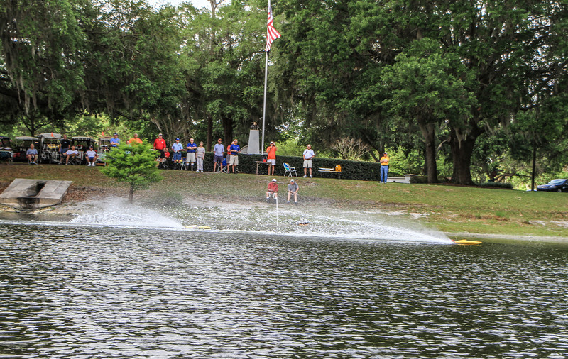 The 2nd boat is between the tree and the 2 guys sitting at the starting line pole, in the spray from the first boat.