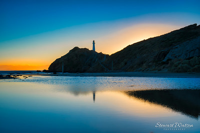 Castlepoint lighthouse reflected in the still waters of the lagoon as the sun rises at first light