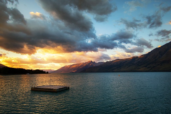 The view looking back towards Queenstown from the Glenorchy Pier as sunrises over Lake Wakatipu and hits the surrounding hills and mountains in the Queenstown Lakes District, Otago