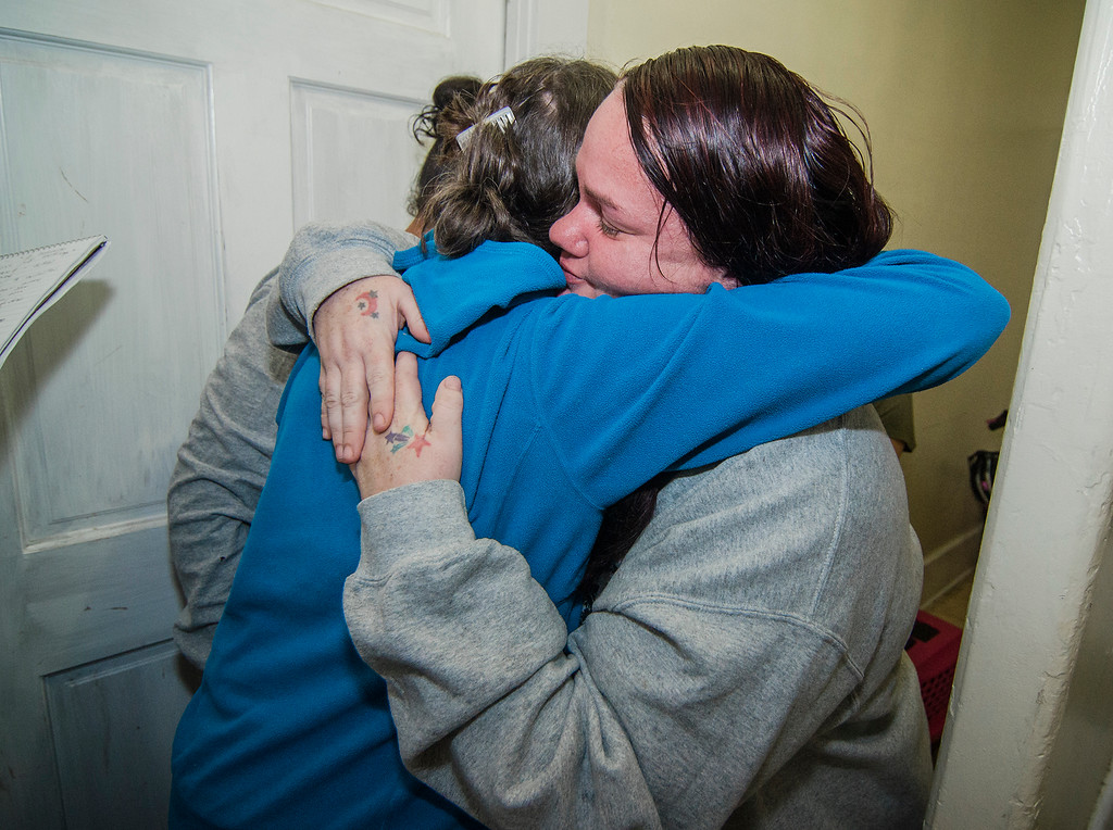. Fitchburg residents Judy Reardon and Kathy Goguen helped reunite Bella, a cat missing for two years, with her owner Marcia Poland, and daughter Trinity, thanks to a microchip on Tuesday, October 24, 2017. Poland embraces Goguen in thanks on Tuesday evening. SENTINEL & ENTERPRISE / Ashley Green