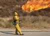 An LA County firefighter pulls a protection line along a freeway offramp during the Sayre Fire.