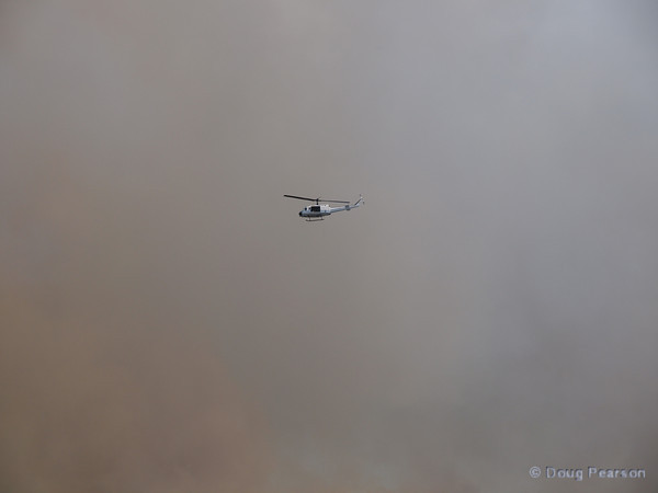 A NASA Helicopter flys over a brush fire at Kennedy Space Center