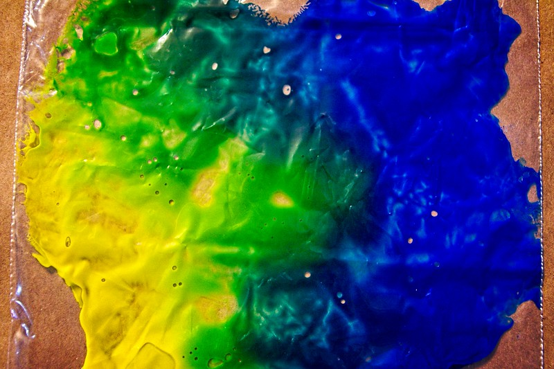 Yellow and blue paint mixed in a bag to make green