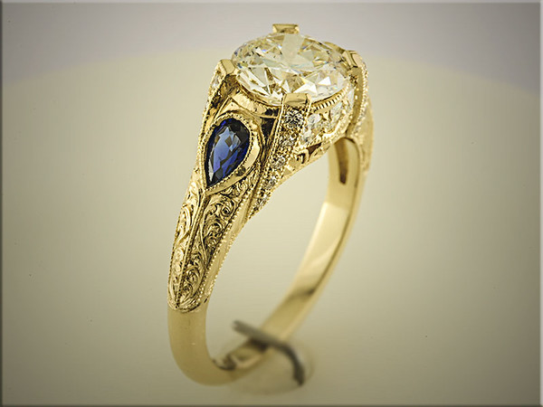 14K yellow custom mounting with customers round diamond in center and 1 tear drop sapphire on each side, made and hand engraved by Ron Litolff