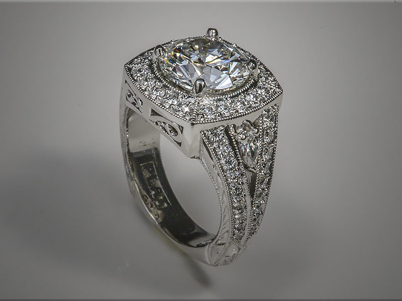 Platinum custom mounting fashioned around a stunning 3.01ct diamond.  Bead and brightcut diamonds around the center in a cushion shape design.  Split shank with diamonds separated by a pear shaped diamond on each side.  Designed, made and hand engraved by Ron Litolff