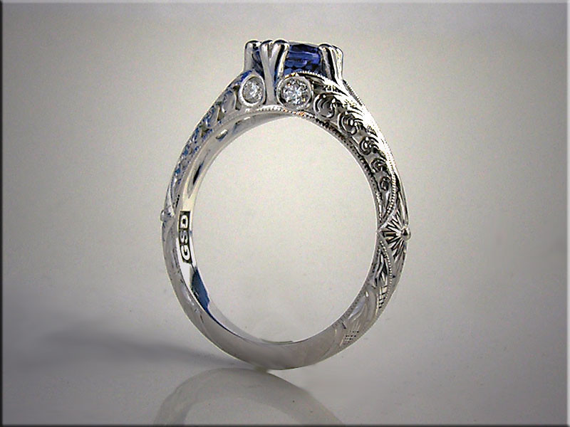 14K white gold 3 dimensional hand engraved scroll design, set with sapphire in center and 4 accent diamonds