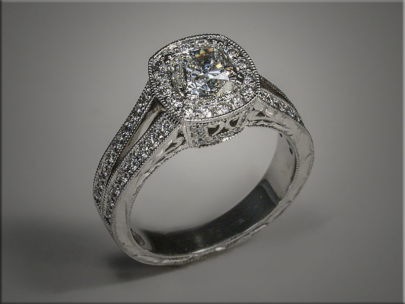14K white gold vintage style engagement ring with cushion shaped diamond in center.  Ideal cut diamonds form a halo around center. Split shank with high shoulders set bead and brightcut style.  Designed, made and hand engraved by Tim Frank.