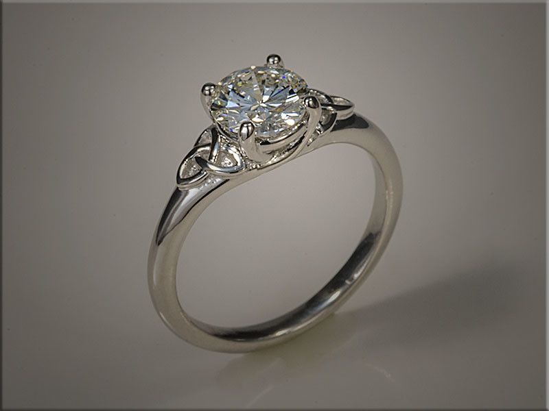 14K Platinum ring with Trinity knots on each side in Trellis style mounting.  Designed and made by Ron Litolff